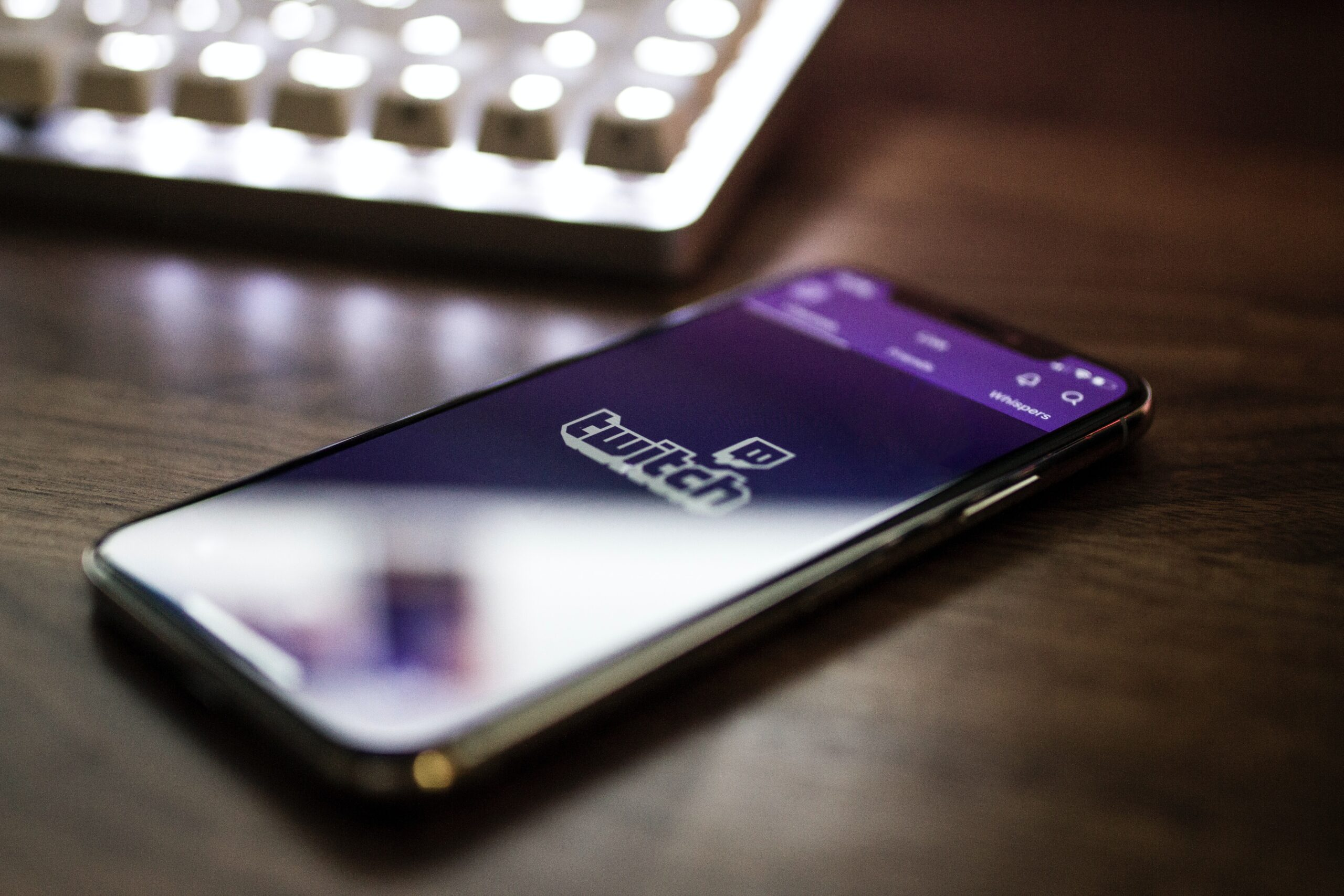 twitch logo on a mobile phone, using royalty free music for streaming on twitch